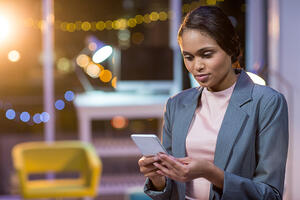Businesswoman text messaging on mobile phone in office at night